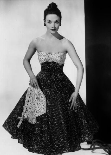 Model wearing a strapless summer dress in a spotted fabric, with a wide flared skirt and matching accessories, 1950. Photo by Chanoner Woods.