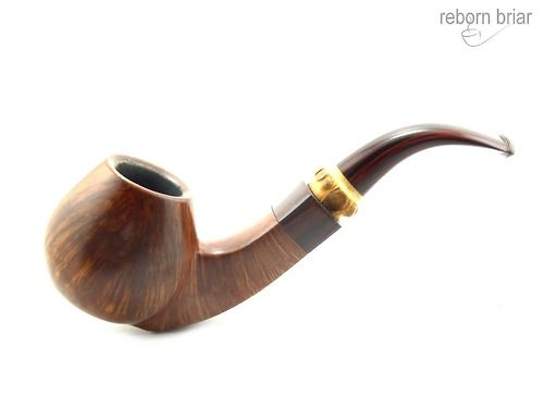 Rainer Barbi started hand carving pipes in 1974 and this is a particularly stunning example of his work. Carved between 1975 and 1981 before he started stamping grades and dates on his pipes. A large and solid bent brandy shaped pipe with gracefully curved square shank. Beautiful straight grain runs all around the bowl and up each side of the square shank. The pipe has been carefully cut and crafted to best display the perpendicular grain in the briar. The base of the pipe is flat so that…