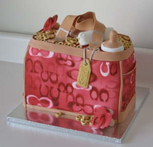 Coach Diaper Bag Cake filled with diapers, bottle, and overflowing cheerios