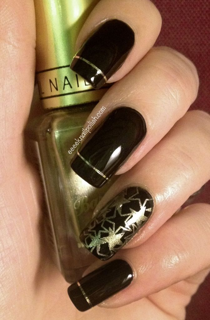 Black nails stamped with gold and one line of golden tape