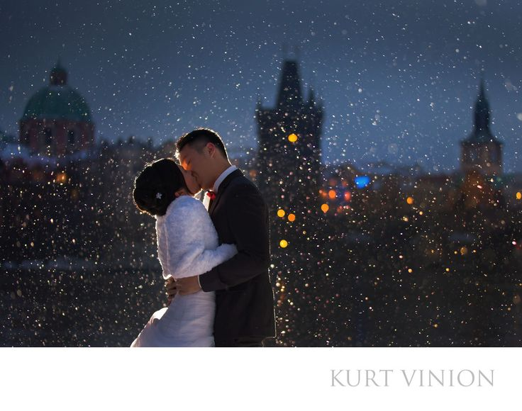 London wedding & Prague pre wedding photographer - winter time pre wedding photos Prague : a couple share an embrace as snow falls during their pre wedding portrait session in Prague. Location: Charles Bridge.