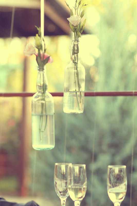 An amazing wedding decor idea: Hanging some pretty little bottles with cute flowers in them; so beautiful!