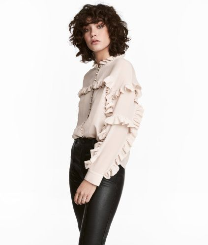 Natural white. Blouse in soft lace. Stand-up collar, opening at back of neck with covered button, ruffle details, and long sleeves. Lined (except sleeves).