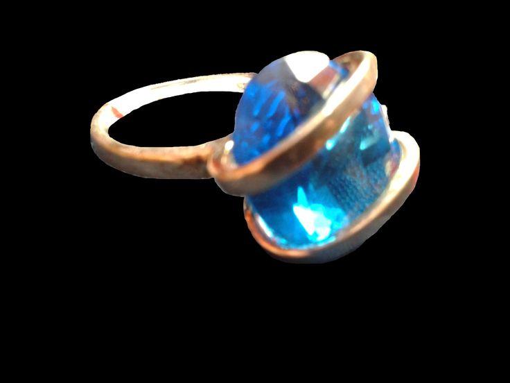 Delicado anillo en plata entrelazando una hermosa piedra en color celeste