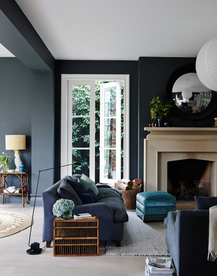 The Pale Stone Of Fireplace Looks So Striking Against Dark Grey Walls