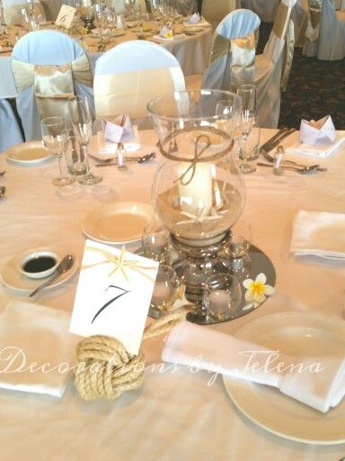 Classic beach style wedding reception centerpiece with nautical table number holder, star fish, shells and frangipani  www.decorationsbyjelena.com.a