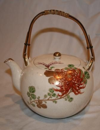 "Vintage Handpainted Asian Teapot | Vintage Duds and Decor. Beautifully painted chrysanthemum in rusts and gold grace this lovely teapot with gold painted accents on the spout, and teapot lid. Bamboo handle finishes the teapot. Small red fret pattern around the base of the teapot. 5 1/2"" diameter 7"" tall including handle. In Perfect condition."