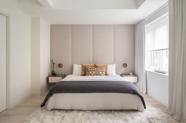 master bedroom with custom nightstands and an upholstered back wall