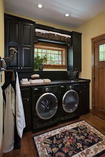 """Black cabinets, black countertop over top black front loading washer and dryer.  The effect is very clean and classic."""