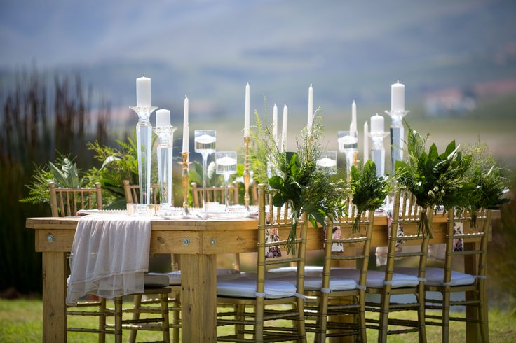 Styled Shoot with a pallet wood table, greenery and floral arrangement on chais, gold, glass and crystal candle holders and floral napkins
