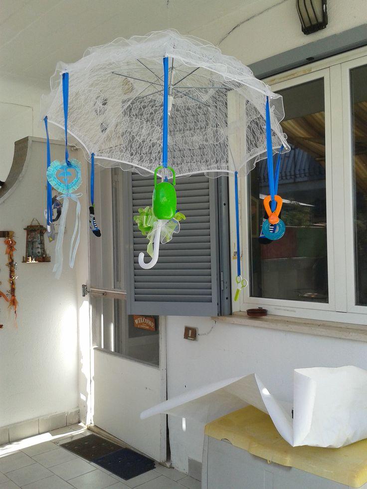Ombrellino baby shower maschietto. Ai nastrini sono attaccatti accessori utili per i primi mesi del bambino