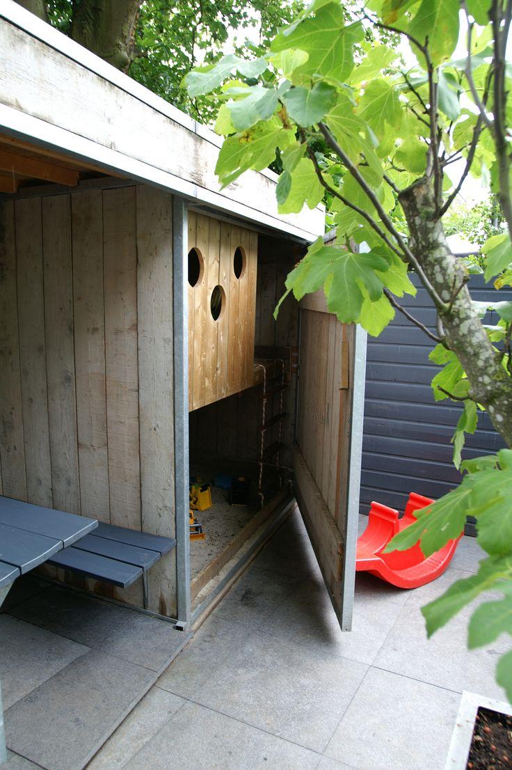 Speelhuisje / zandbak mooi weggewerkt achter  een deur van steigerhout.  Ontwerp en aanleg hoveniersbedrijf van Elsäcker  Tuin. www.tuintuintuin.nl
