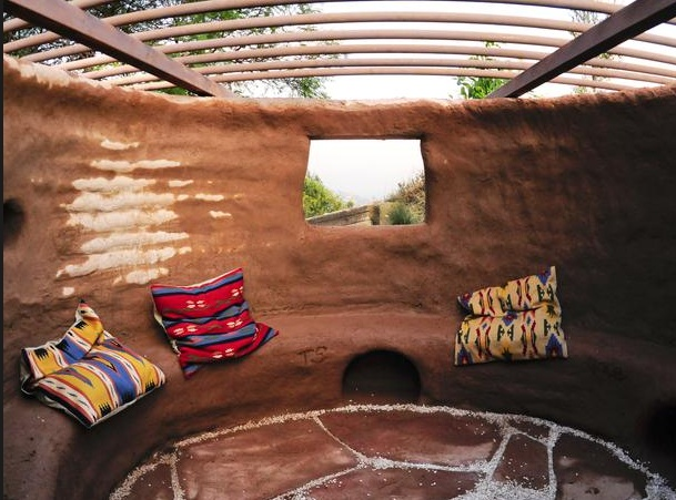 This outdoor adobe lounge area is an intimate space yet has an open roof and a nice view of the scenery.