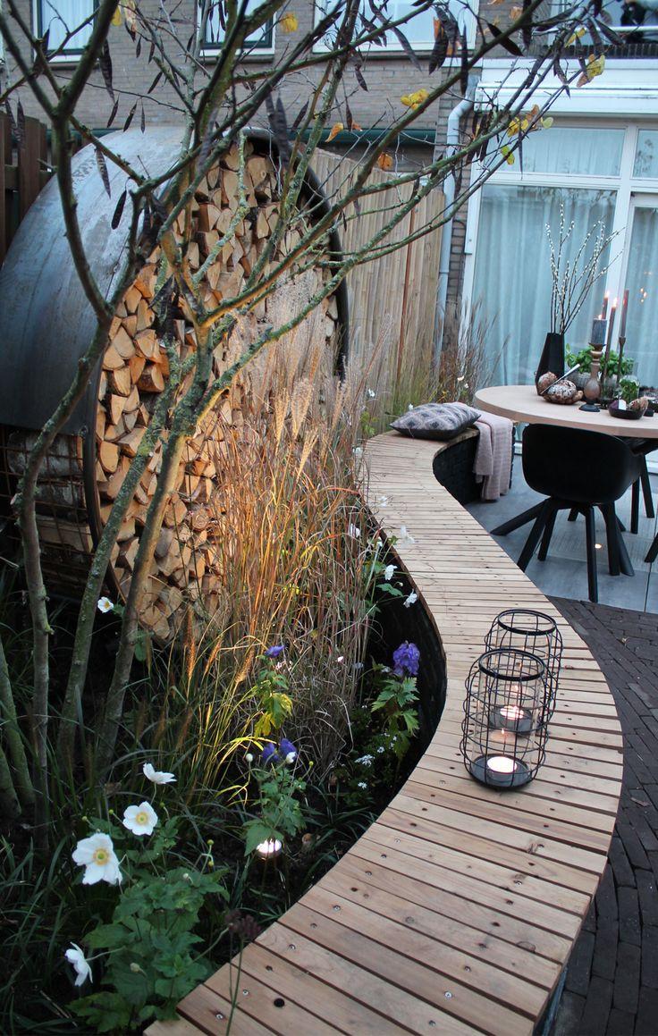 Romantische tuin gemaakt bij Eigen Huis & Tuin. Veel sfeer, hout, verlichting, borders en siergrassen. Ook een vuurschaal en loungehoek zorgen voor extra romantiek, ook in de winter.