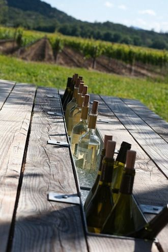 Retrofitted old picnic table with a galvanized steel wine cooler built into one of the slats... Great Idea!