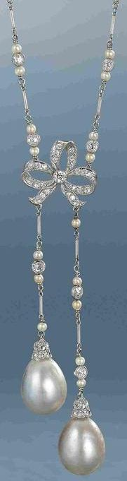 A natural pearl and diamond lavallière, circa 1910.  The fine chain composed of old brilliant-cut diamond and seed pearl trios, connected by platinum baton links, suspending a central old brilliant-cut diamond bow motif, terminating in two natural pearl drops of unequal length, diamonds approximately 3.10 carats total, one diamond a later paste replacement, necklace length 53.0cm. Via Bonhams.