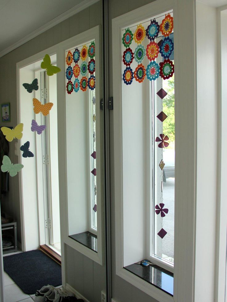 Pequeña cortina, a modo de bandó, sobre barra. Aplicaciones multicolores de ganchillo.