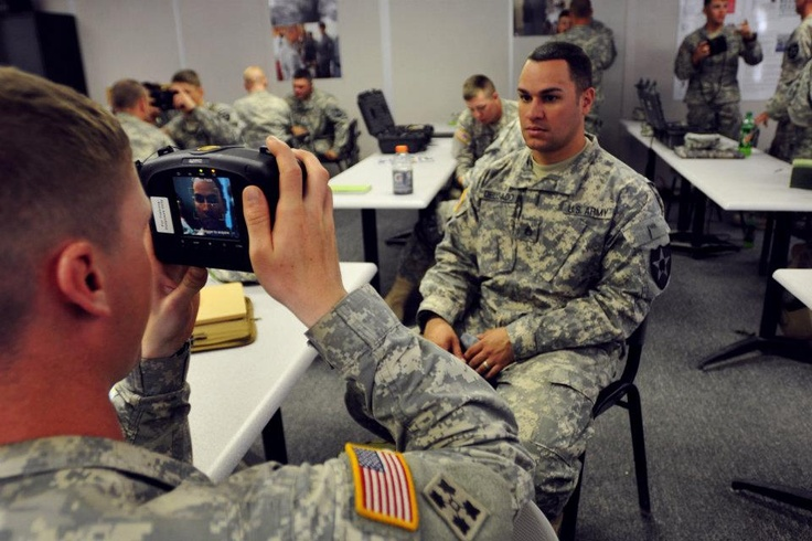 Sgt. Mason Bischoff photographs the face of Staff Sgt. Mike Delgado with Handheld Interagency Identity Detection Equipment (HIIDE) during a HIIDE class here, June 5. The Soldiers, both with Headquarters and Headquarters Company, 4th Stryker Brigade Combat Team, 2nd Infantry Division, participated in the class as a part of Reception, Staging, Onward Movement, and Integration (RSOI) for their rotation at the National Training Center here.