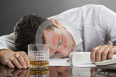Portrait of tired overwhelmed young man sleeping at work with glass of alcohol on desk. Selective focus on the glass.