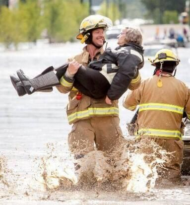 Calgary fireman evacuating flood victims June 21, 2013.  This one of the best photos of our amazing emergency workers! Apparently she was saying to him she hasn't been carried like this since her wedding day. So cute!!!