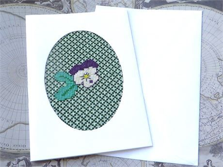 A large cross stitch card, 5 x 7 inches,which is white with an oval window.   A viola or pansy flower in purple and whiteon a pale green fabric, surrounded by dark green lattice work.
