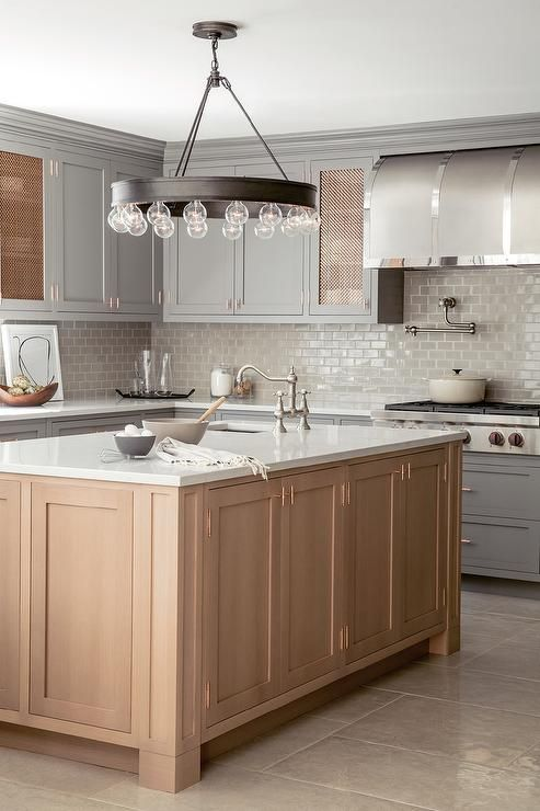 Beautiful kitchen features gray shaker cabinets paired with white quartz countertops and a gray brick tile backsplash.