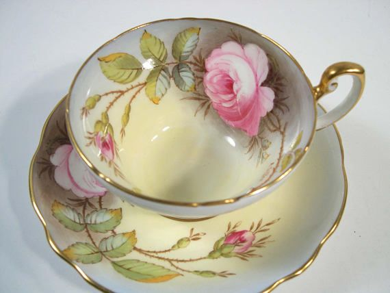 Lovely tea cup and saucer made by Foley, England. From greyish blue to yellow, there is a large pink rose standing out on the blue. The set is signed A, Taylor The backstamp date this set to 1948 - 1963 The tea cup is 2 1/4 high and the saucer is 5 5/8 diameter The rims and handle