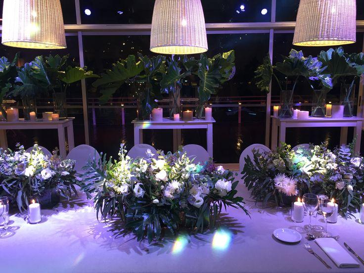 Mesa principal con fondo de arreglos de hojas, centros rectangulares sobre mantel de lino. Iluminado por pantallas de ratan.