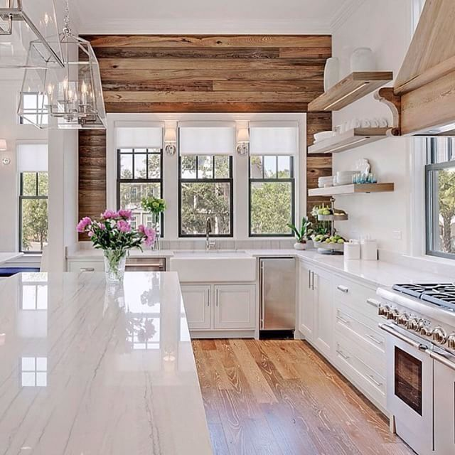 White with character- I love the wood wall. Farm sink? Check.  White marble/Quartz countertops? Check. Wood floors? Check.  Stainless appliances? Check.  Pretty lights? Check.