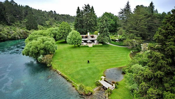 Manicured lawns and the deep turquoise Waikato River.