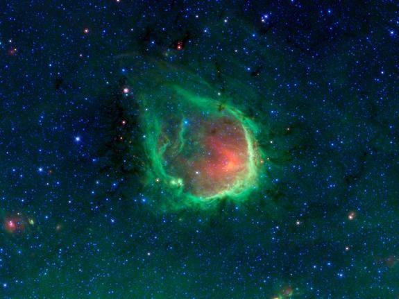 """Nebulosa esmeralda brilhante vista pelo Telescópio Espacial Spitzer da NASA é uma reminiscência de um anel brilhante. Os astrónomos acreditam que anéis como este são realmente esculpidas pela luz poderosa de gigantes estrelas """"O"""". Estas estrelas são o tipo mais maciço de estrelas conhecidas."""