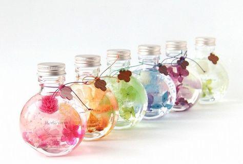 コロンとした丸みのあるガラス瓶でペーパーウエイトにも丁度いいサイズです。斜めに傾けて置く事も出来色々な表情が楽しめます。集める楽しみもあるかわいいボトル、6色展開です。ご希望のお色(1枚目の画像左からピンク・オレンジ・グリーン・ブルー・パープル・ホワイト)を備考欄へご記入ください。色集めしたり、他のハーバリウムと合わせたり揃える楽しみもございます。傾けるとオイルの中でゆったりと中の植物が動きます。そして透明感のあるオイルの中で綺麗な状態を長く楽しめる、植物インテリアとして今とても人気です。明かりにかざすとまた別の表情を楽しめいつまでも見つめていたくなる事と思います。瓶の口元には花のチャームを付けてFlocon de niegeオリジナルな可愛らしい雰囲気を楽しんでいただけたら嬉しいです。(チャームはピンク・ライトブラウン・ダークブラウン画像の組み合わせです)母の日・父の日・ 敬老の日 ・各種お祝い ・新築祝い・ 結婚祝い・ちょっとしたお礼もちろんご自分用にインテリアとして玄関・キッチンやトイレにもお勧めです。花材:プリザーブドフラワー&ドライフラワーを使用…
