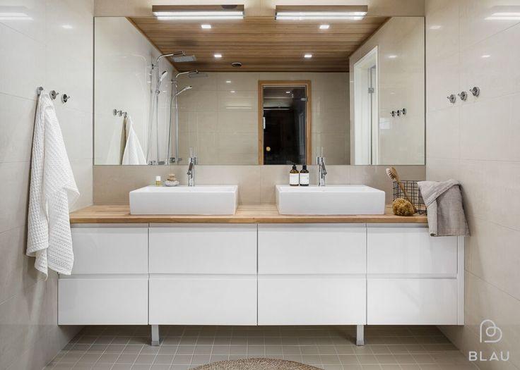 Espoon Friisilän remontoitavan omakotitalon saunaosasto kalustettiin puhtaan valkoisella ja lämpimällä puulla. Nämä sopivat täydellisesti maanläheisen hiekan väristen laattojen kanssa.