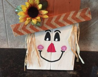 Handmade wood wooden Scarecrow with a cute hand painted face and a sunflower with burlap on the hat. Scarecrow is made from reclaimed lumber that has been distressed. Measures 19 tall. Does not include the ghosts or pumpkins. Those items are also for sale on my site.