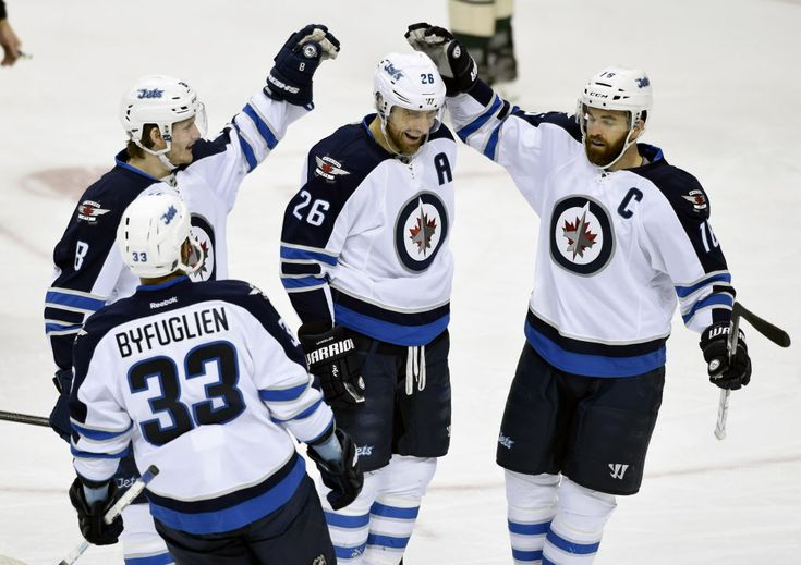 Jan.15 2016 - Jets 1 - Wild 0 - Winnipeg Jets' Dustin Byfuglien (33), Jacob Trouba (8) and Andrew Ladd (16) congratulate right wing Blake Wheeler (26) on a goal against the Minnesota Wild during the first period in St. Paul, Minn - Tired Jets gut out big win - Winnipeg Free Press