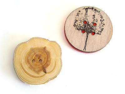 O botão da esquerda é feito de zimbro e foi comprado numa banquinha de artesanato feito em zimbro em Covent Garden - paragem obrigatória a qualquer pessoa que vá a Londres.  O botão da esquerda veio da Ray Stitch. É em madeira gravada e resina transparente por trás.