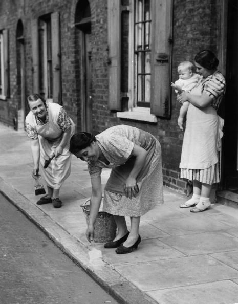 9th September 1939: Housewives of Roupell Street, London, painting kerbs white to help night time traffic during WW II. (Photo by Harry Todd/Fox Photos/Getty Images) #london #war #East_End