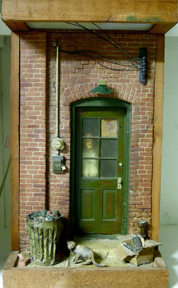 A unique piece from the Michael Garmin Collection - this three-dimensional wallmounted sculpture depicts a vintage doorway with a gentleman peering outside. There are two small lights that are housed in the top area of this piece that are turned on with a switch on the electrical cord that illuminates the scene. This diorama looks so authentic and has so many wonderful details. The building is old brick and has a wonderful worn wood door with a broken pane that has been boarded up. There is…