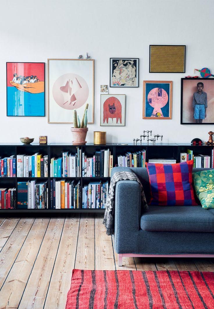 Colorfull living room a beautiful wall art, bookshelves and hardwood floors.