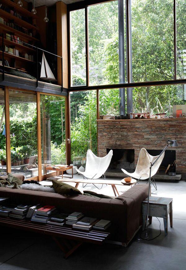 modern cabin butterfly chairs, big windows, lots of greenery, stone, dark brown. Just beautiful.