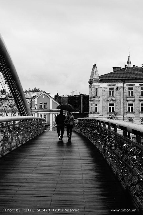 """Together under the rain"" (2014) by Vasilis D.  Kraków, Poland Kładka o. Laetusa Bernatka  URL: www.artfot.net Follow me on twitter: www.twitter.com/vasilisbiz  #afternoon #streetphotography #landmark #bridge #river #Krakow #Poland #blackandwhitephotography #Kladka #Kładka"