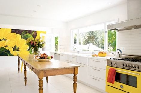 yellow kitchens with white cabinets | Bobbie Burgers kitchen from House & Home.  Love the sweep of white broken by the yellow and black art and yellow stove