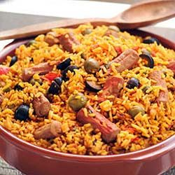 ARROZ CON SALCHICHA VIENA -- RICE WITH VIENNA SAUSAGE Yield: 8-10 servings #Cuban 2 large green peppers 1 large onion 4 cloves garlic, minced 4 small roma tomatoes chopped 1 teaspoon salt 1/4 cup olive oil for frying (some also use lard) 4 cups rice 3 cups ham broth 1 cup white wine 1 cup tomato sauce 1/2 teaspoon Bijol Powder 5 cans Vienna sausage links, sliced in half green and black pitted olives (optional)====