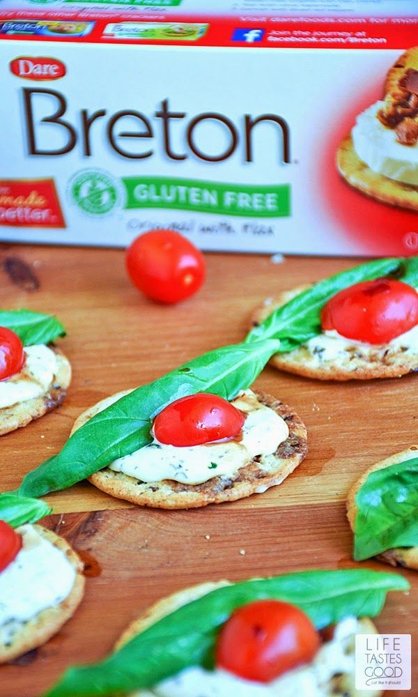 Caprese Crackers   by Life Tastes Good are gluten free, bite sized morsels of deliciousness! Topped with a garlic and herb cheese spread, fresh basil leaves, tomatoes, and a drizzle of balsamic dressing, these appetizer bites are tasty any time of day, and especially perfect for a party, as they are easy to make and so enjoyable to eat!