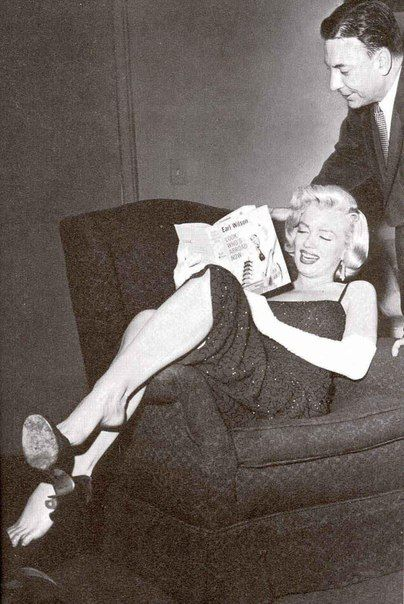 Marilyn Monroe sitting in a chair and reading
