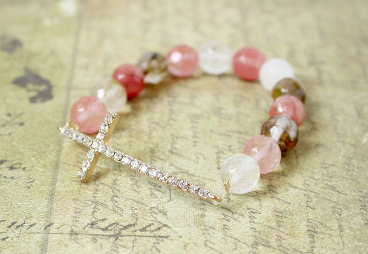 A collection of multi-color watermelon crystal beads that are a beautiful compliment to a gold sideways cross...it's full of sparkle and shimmer! Gold Sideways Cross Bracelet