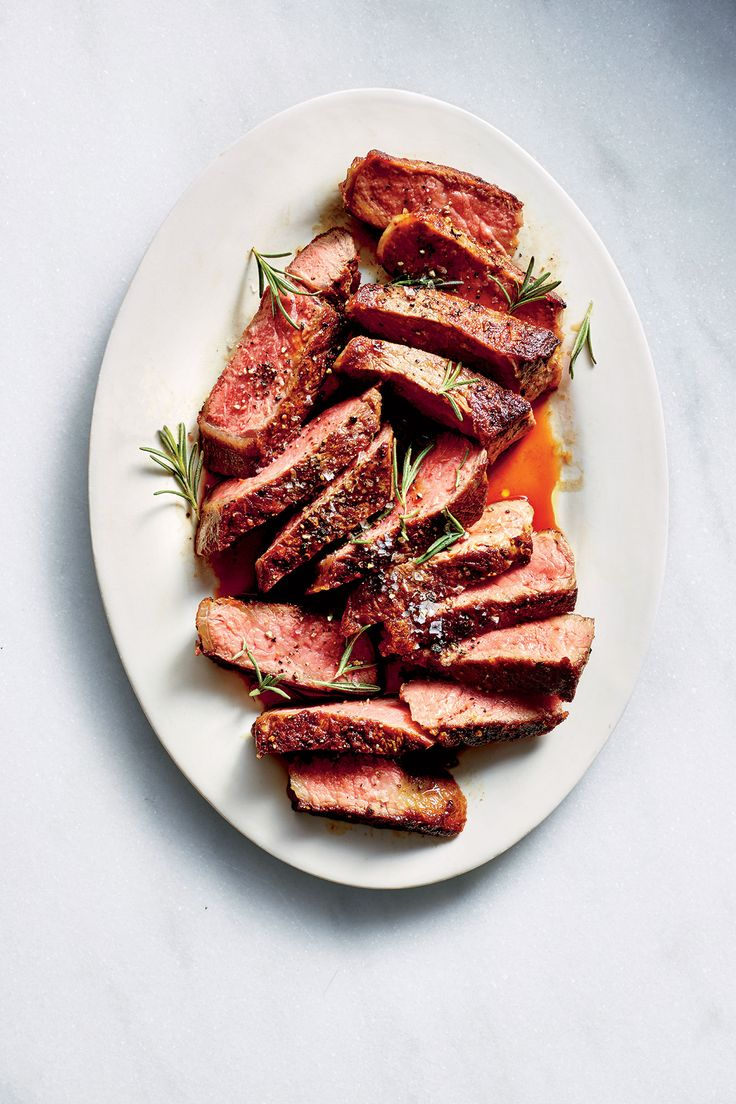Garlicky New York Strip Steak | To make your next steak night a guaranteed success, be sure to watch over the temperature of the meat with a thermometer. This works best on steaks of 1 inch (or more) thickness, as it's hard to get a good reading on anything thinner. And salt the steak purposefully for a bigger flavor boost. We marinate the meat with lemon juice, garlic, and olive oil—but no salt, because the marinade will get discarded. Instead, we sprinkle on a little kosher salt before