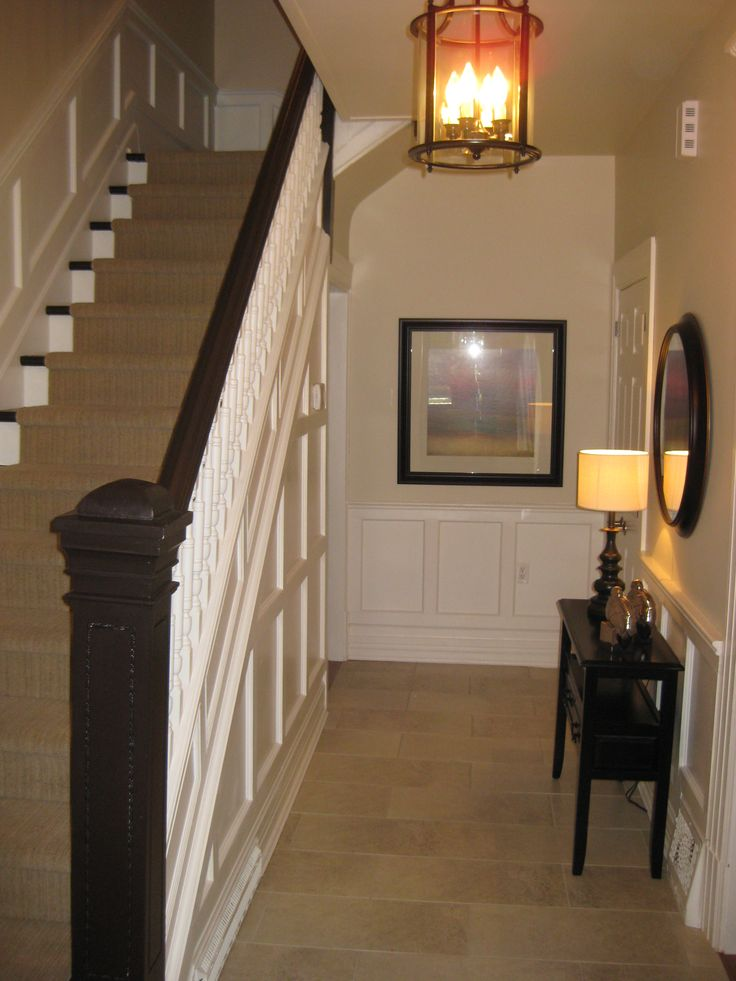 Old staircase and new wainscotting gets a fresh coat of paint. If you have a long narrow hallway then try a long narrow table and keep your space clean and open. A great place to put a tiny lamp add more light.