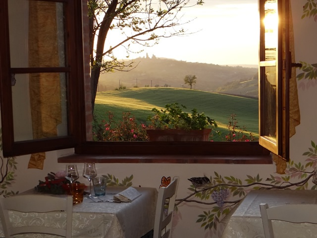 Vista al tramonto da una delle finestre del ristorante romantico Taverna di Bibbiano con vista su San Gimignano (Siena) e sulla campagna toscana. Loc. Bibbiano la Taverna, 35 - Colle di Val d'Elsa (Siena)