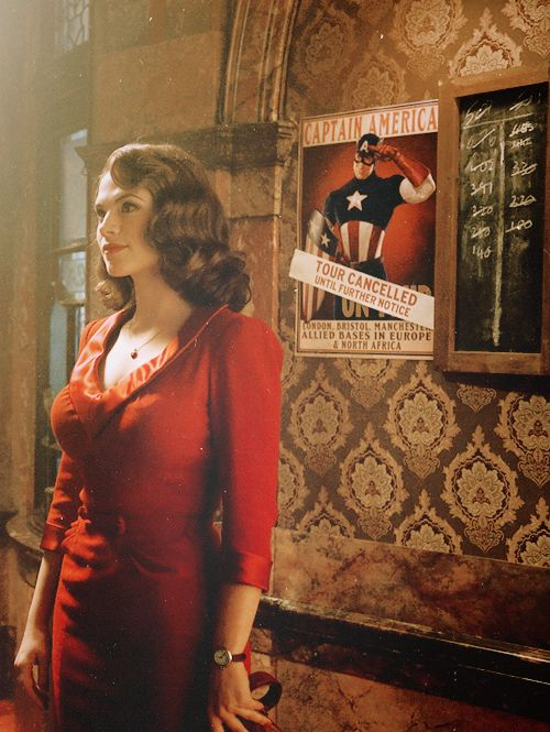 'Peggy Carter' in front of a 'Captain America' poster in 'Marvel's: Agent Carter' - Visit to grab an amazing super hero shirt now on sale!